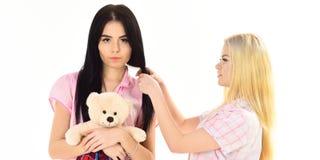 Soeurs, meilleurs amis dans des pyjamas faisant la tresse, coiffure Les dames sur les visages de sourire avec l'ours de jouet de  Photos libres de droits