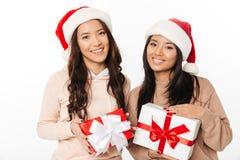 Soeurs mignonnes asiatiques de dames utilisant des chapeaux de Santa de Noël Photos libres de droits
