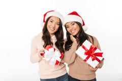 Soeurs mignonnes asiatiques de dames utilisant des chapeaux de Santa de Noël Image libre de droits
