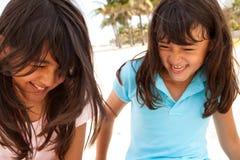 Soeurs mignonnes jouant à la plage sur le sable Image stock