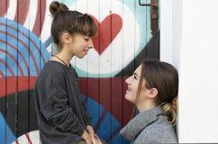 Soeurs regardant l'un l'autre avec un sourire Photographie stock libre de droits