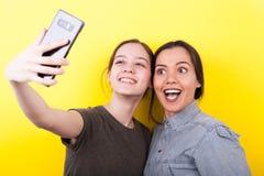Soeurs riantes et de sourires heureuses prenant un selfie Photo libre de droits