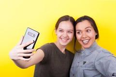Soeurs riantes et de sourires heureuses prenant un selfie Image stock
