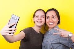 Soeurs riantes et de sourires heureuses prenant un selfie Images libres de droits