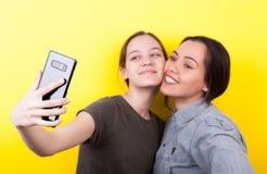 Soeurs riantes et de sourires heureuses prenant un selfie Photos libres de droits