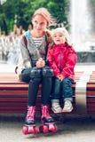 Soeurs s'asseyant sur le banc Photographie stock libre de droits