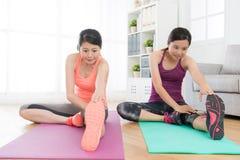 Soeurs s'asseyant sur le plancher de salon faisant le yoga Photo libre de droits