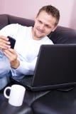 Sofà degli uomini con uso del calcolatore e del telefono. Fotografia Stock