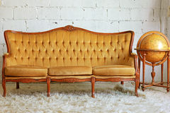 Sofà della mobilia dell'annata con il globo Immagini Stock