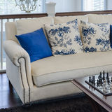 Sofà di lusso con il cuscino blu su tappeto marrone in salone Fotografia Stock