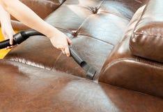 Sofà di pulizia della donna con l'aspirapolvere Immagine Stock