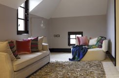 Sofà e sciarpa di svago nella camera da letto della soffitta immagine stock libera da diritti