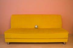 Sofà giallo con piccolo discoball Fotografie Stock