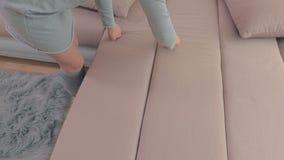 Sofà pulito della donna con il rullo del residuo di stoffa