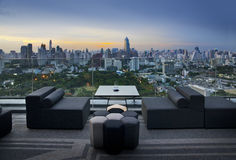 Sofà sul terrazzo che trascura parco e costruzione verdi, Bangkok, Tailandia Fotografia Stock