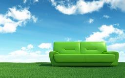 Sofà verde sul campo di erba Immagini Stock Libere da Diritti
