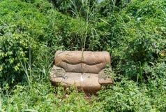 Sofá abandonado en la hierba Fotografía de archivo