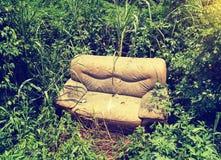 Sofá abandonado en la hierba Fotos de archivo