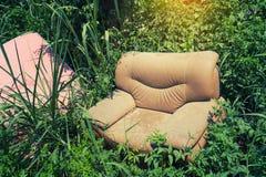 Sofá abandonado en la hierba Fotografía de archivo libre de regalías