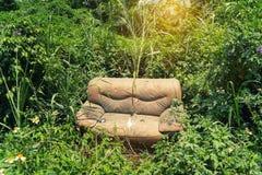 Sofá abandonado en la hierba Imagenes de archivo