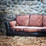 Sofá abandonado no lado da construção imagem de stock