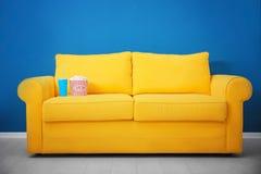 Sofá amarelo com pipoca e bebida no cinema home Fotos de Stock Royalty Free