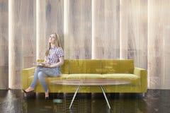 Sofá amarelo em uma sala de visitas de madeira, mulher Imagem de Stock
