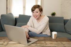 Sofá atractivo y feliz joven del sofá de la mujer en casa que hace una cierta sonrisa del trabajo del ordenador portátil relajada fotografía de archivo libre de regalías