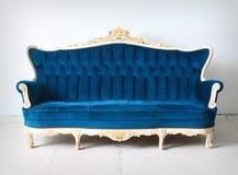 Sofá azul de la vendimia en el cuarto Foto de archivo