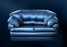 Sofá azul em um preto Fotos de Stock Royalty Free
