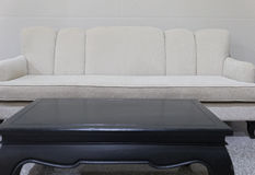 sofá beige del sofá de la tela y escritorio negro Fotos de archivo
