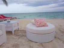 Sofá blanco y almohada roja en la playa foto de archivo