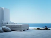 Sofá branco que está em um pátio com opinião do seascape Imagens de Stock Royalty Free