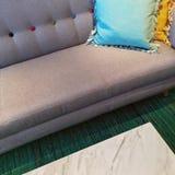 Sofá cinzento com os coxins azuis e amarelos Fotos de Stock Royalty Free