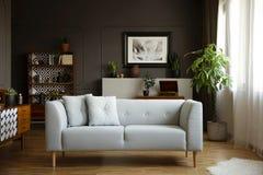 Sofá cinzento com os descansos no interior brilhante da sala de visitas do vintage com plantas e cartaz Foto real foto de stock royalty free