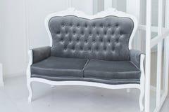Sofá cinzento em um fundo branco da parede Foto de Stock