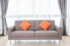 Sofá cinzento na sala de visitas moderna ao lado da janela Deco interior Imagem de Stock