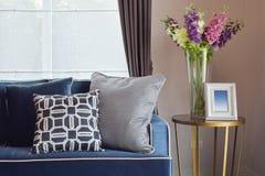 Sofá clásico moderno de los azules marinos y almohadas retras, grises y azules con un florero precioso de la orquídea Foto de archivo libre de regalías