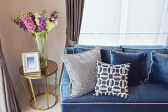 Sofá clásico moderno de los azules marinos y almohadas retras, grises y azules con un florero precioso de la orquídea Imagen de archivo