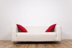 Sofá com descansos vermelhos imagem de stock