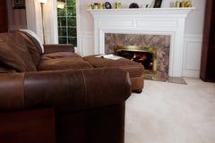 Sofá Comfy pelo incêndio da sala de visitas fotografia de stock royalty free