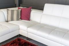 Sofá con la tapicería blanca y dos almohadas imagenes de archivo