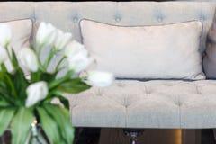 Sofá con las almohadas y la flor, decoración interior del hogar Imagen de archivo libre de regalías