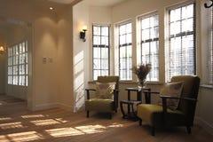 Sofá con las almohadillas por la ventana Imagen de archivo libre de regalías