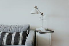Sofá confortável em uma casa moderna com uma lâmpada em uma prateleira branca pequena e um livro com uma cachoeira fotografia de stock royalty free