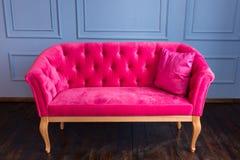 Sofá cor-de-rosa em um fundo azul da parede imagens de stock royalty free