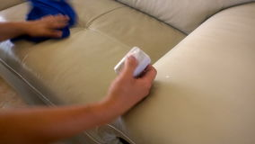 Sofá da limpeza com esponja e pano filme