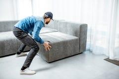 Sofá da montagem do homem no apartamento fotografia de stock royalty free