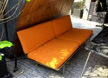 Sofá de couro alaranjado decorado no jardim fotos de stock royalty free