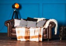 Sofá de couro com coxins claros imagens de stock
